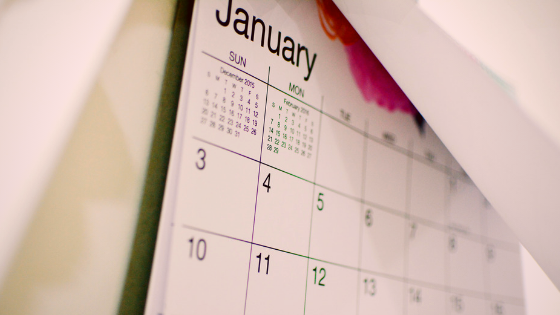 a white calendar with black text partially open to show the month of January
