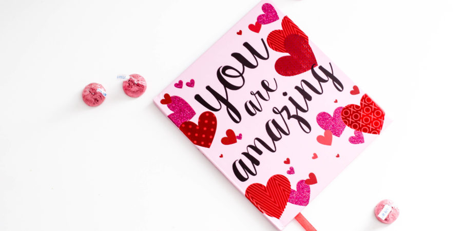 Pink card with various red hearts that reads You Are Amazing in script surrounded by pink Hershey's kisses on a white background