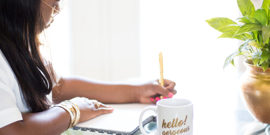 Black woman in gold bracelets writing in a book with a white mug that reads hello gorgeous