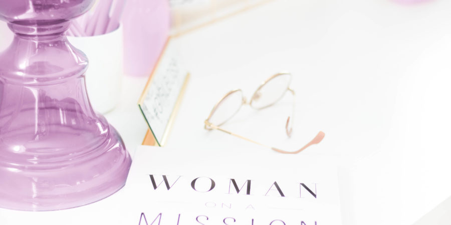 woman on a mission book near purple glass vase and gold rimmed glasses